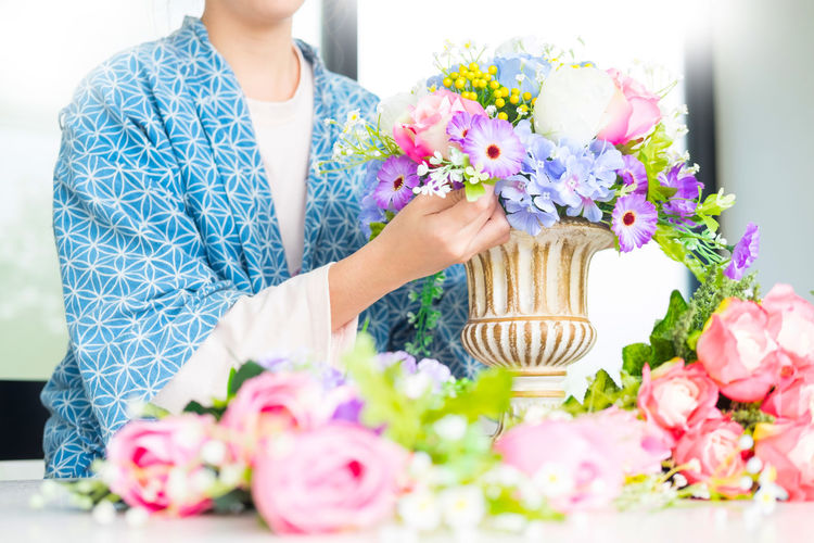 Midsection Of Woman Arranging Flowers In Vase