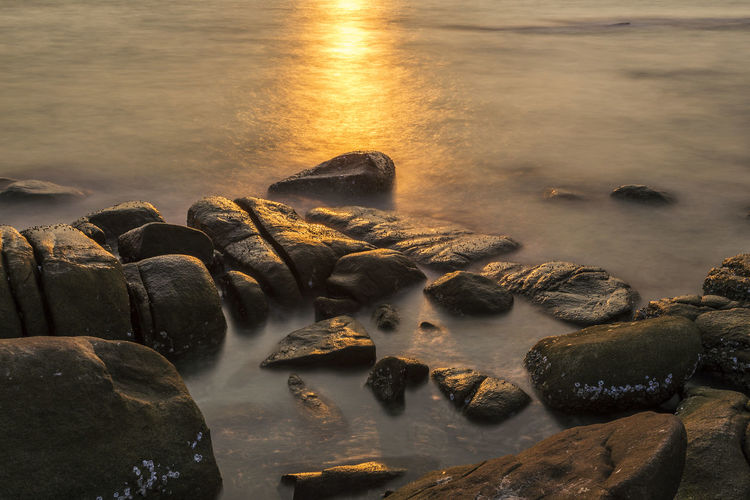 Reflection of sun light in sunset time over the rocks and sea water, Shoot with low shutter speed Beach Beauty In Nature Day Flowing Flowing Water Idyllic Land Long Exposure Motion Nature No People Outdoors Pebble Rock Rock - Object Scenics - Nature Sea Shallow Solid Stone Sunset Water Wet