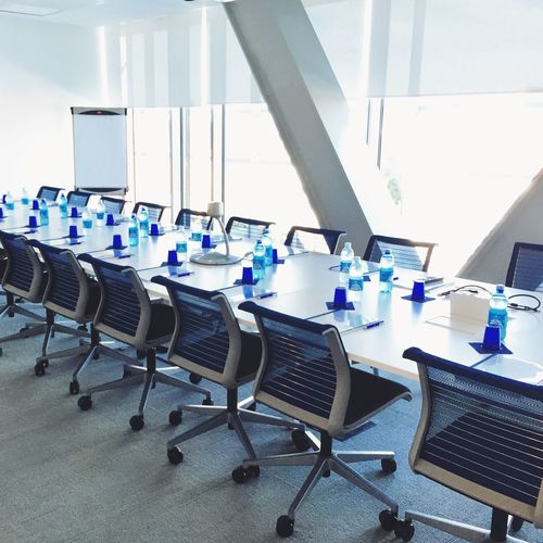Empty chairs by bottles on conference table
