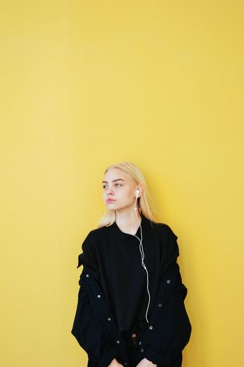 Beautiful young woman standing against yellow wall