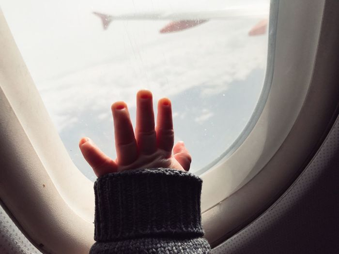 Close-up of hand on window of airplane
