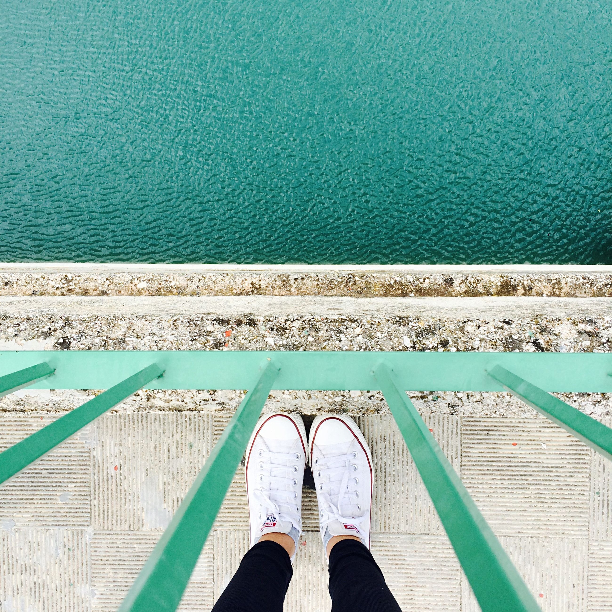 low section, railing, personal perspective, blue, person, water, human foot, pier, wood - material, shoe, high angle view, standing, sea, day, part of, boardwalk, built structure