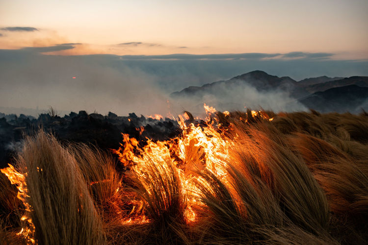 Panoramic view of bonfire on mountain against sky during sunset