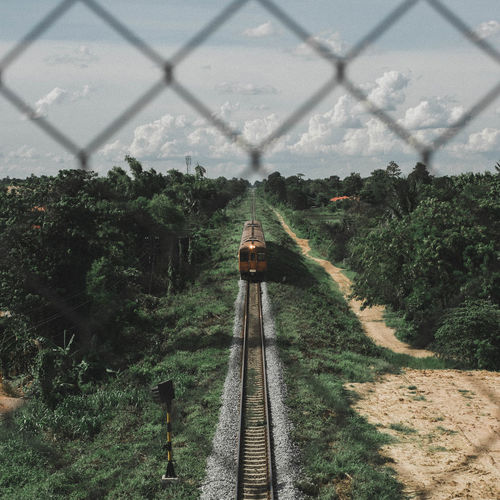 High angle view of train moving amidst trees against sky seen through fence