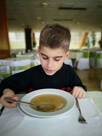 Cute boy having soup on table at restaurant