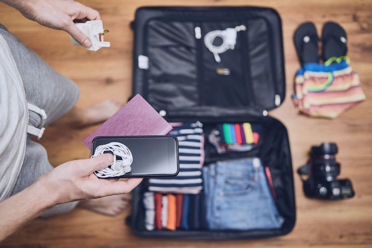 Low section of man packing luggage at home