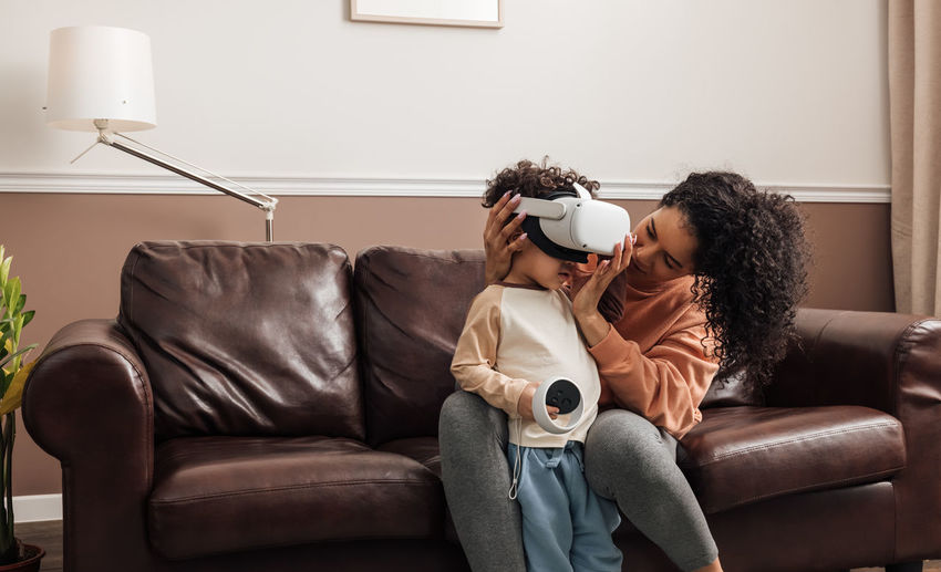 Mother helping son wearing virtual reality headset