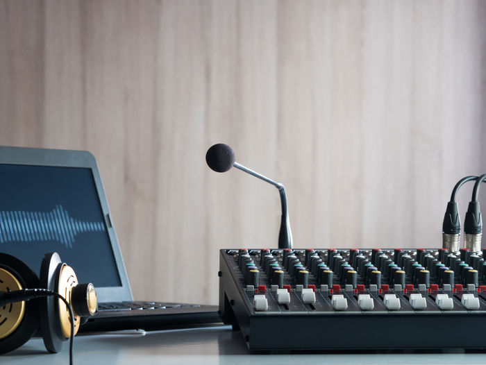 Close-up of sound mixer and microphone on table against wooden wall