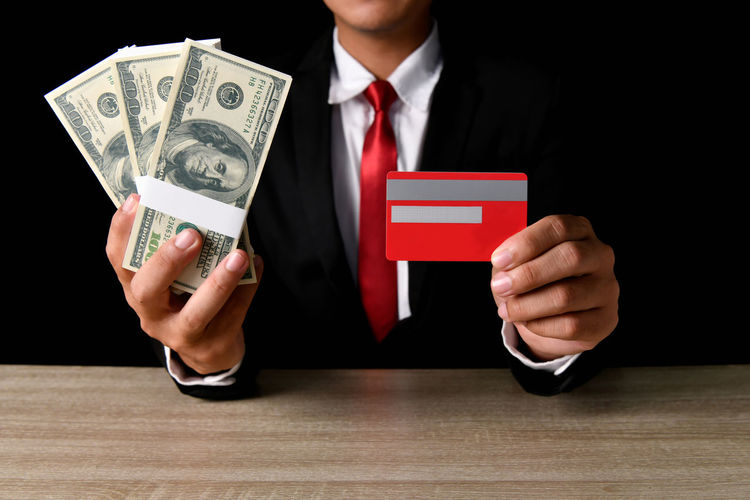 Midsection of man holding money and credit card