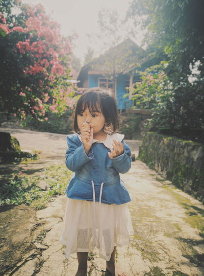Girl Eating Ice Cream While Standing Against Trees
