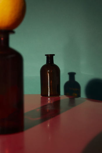 Close-up of glass bottle on table against wall