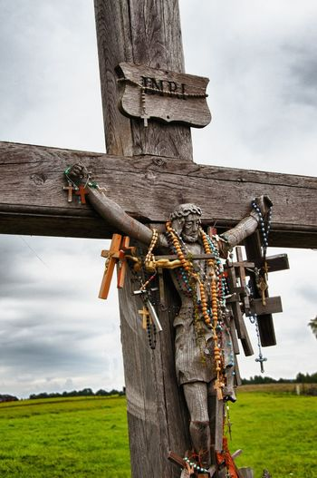 Crosses and beads hanging on wooden crucifix against sky