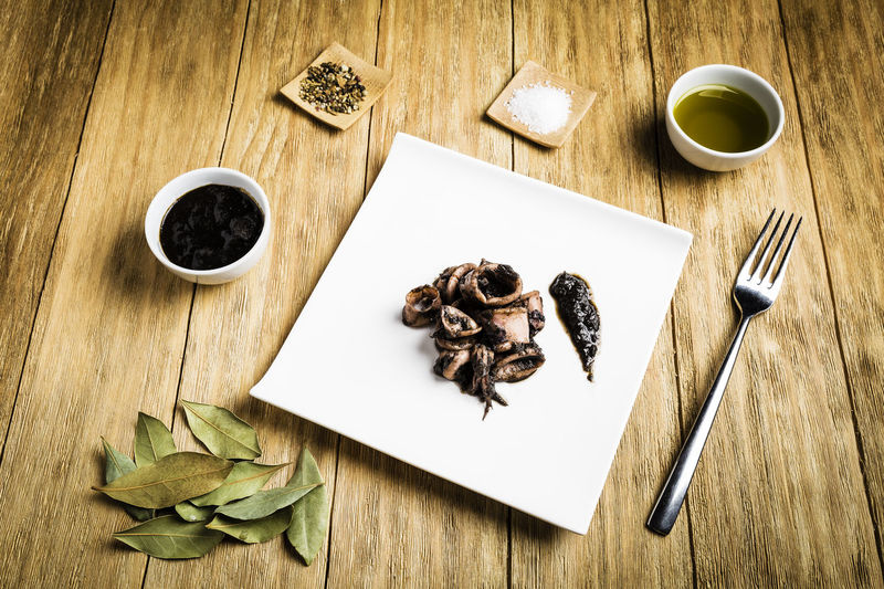 Squid cooked on a white plate with a fork, a bowl with ink, a bowl of oil, salt, spices