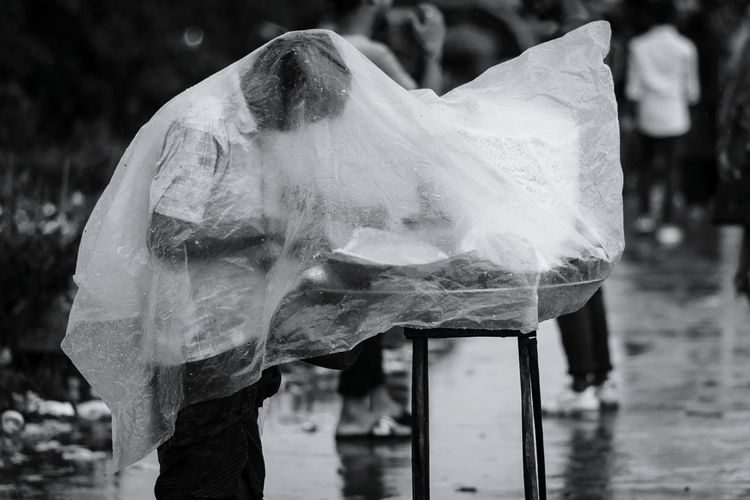 Side View Of Man Covering With Plastic While Standing On Street During Rainfall