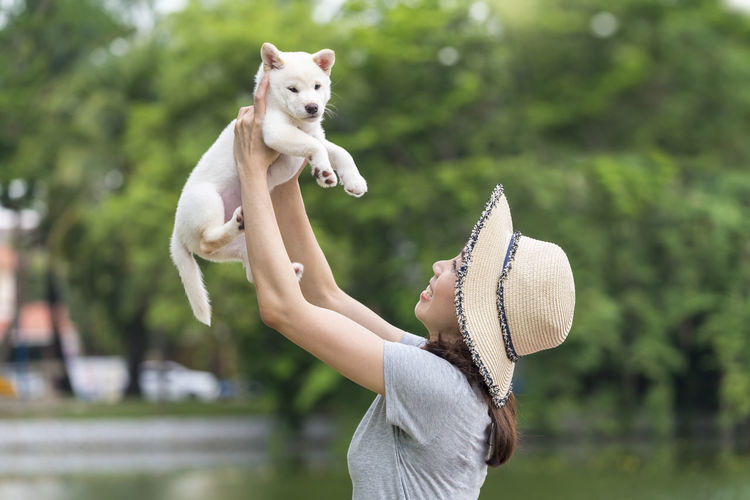 Woman playing with dog while standing outdoors