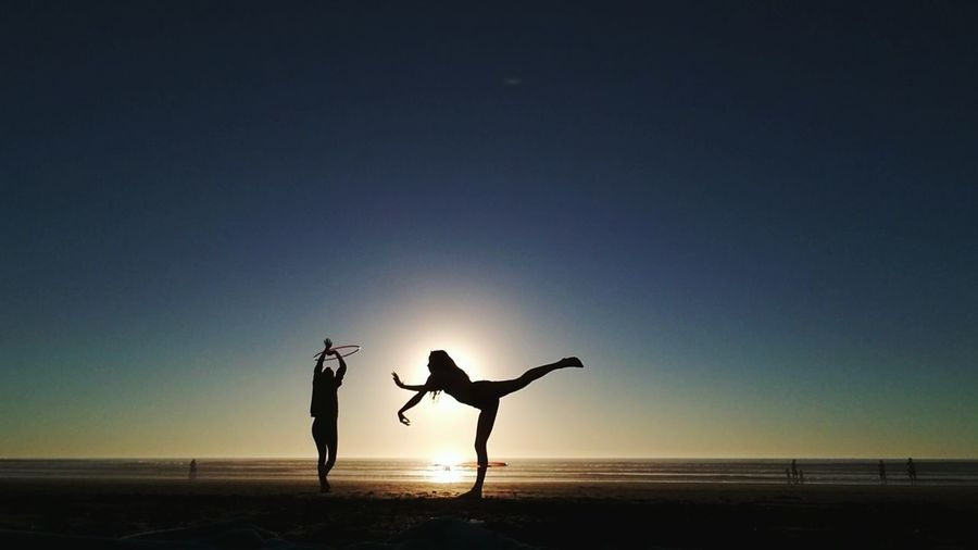Silhouette People Dancing At Beach Against Clear Sky During Sunset