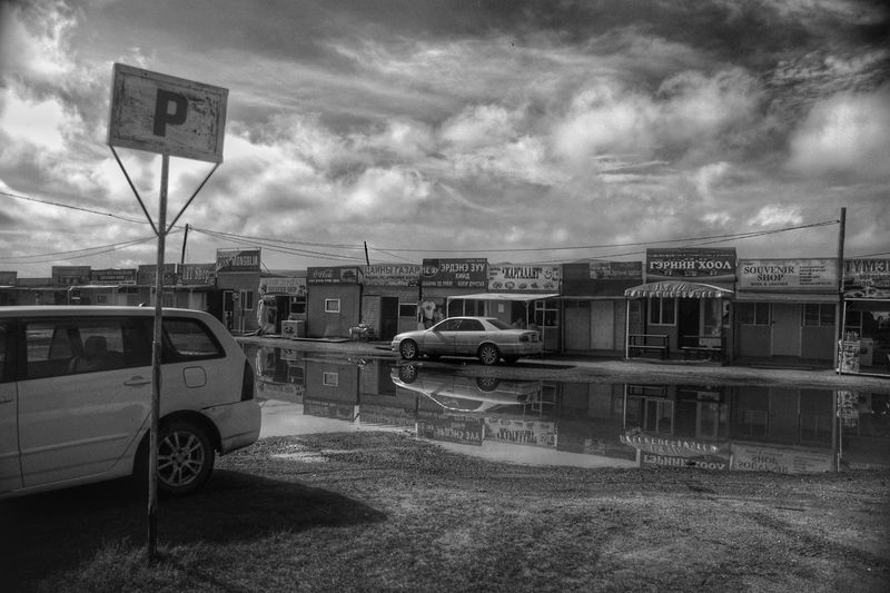 Black And White Mongolia Монгол улс Outdoors Day Mode Of Transportation Car Parking Lot Shops Puddle After The Rain City Land Vehicle Car Sky Cloud - Sky Road Sign