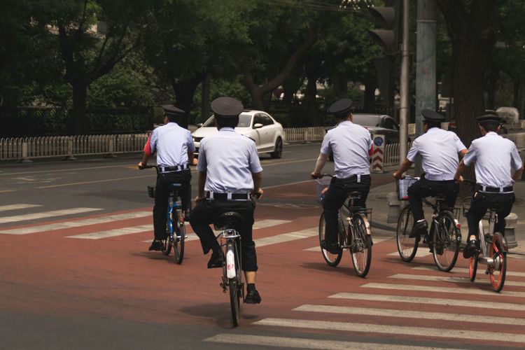 Rear view of people riding bicycle on road in city