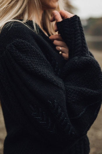 Midsection of woman wearing sweater in winter