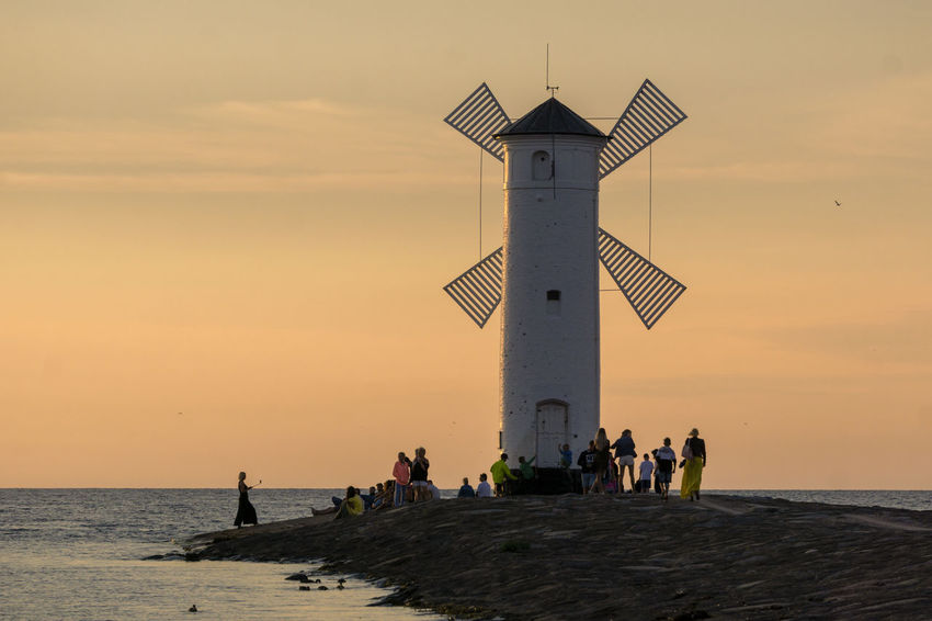 Baltic Sea Stawa Mlyny Tranquility Architecture Built Structure Crowd Group Of People Horizon Over Water Large Group Of People Leisure Activity Lifestyles Nature Orange Color Outdoors Real People Romantic Sky Scenics - Nature Sea Sky Sunset Tower Travel Destinations Water