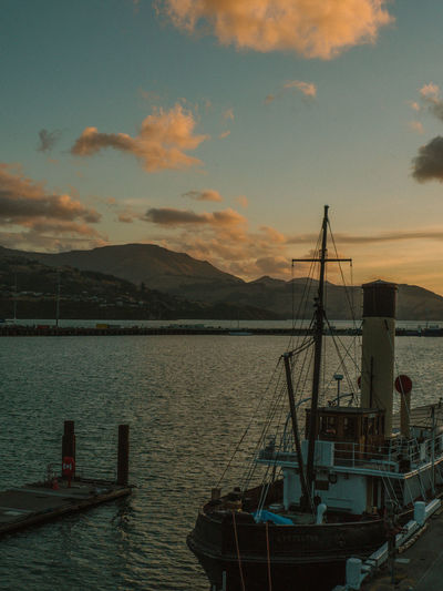 Boats moored in sea against sky during sunset
