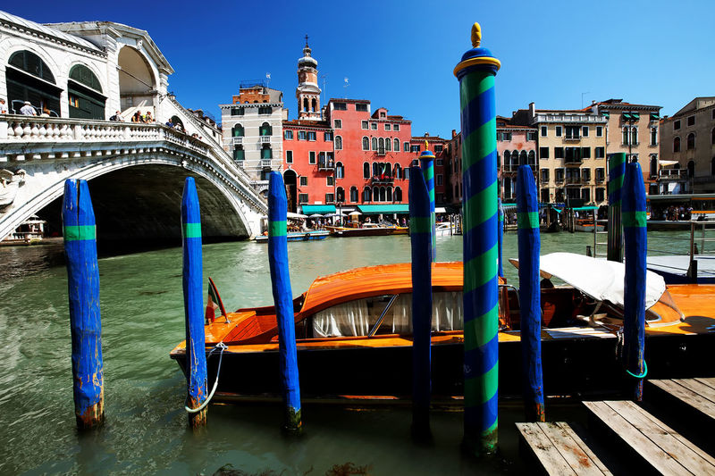 Blue wooden posts by boat in grand canal