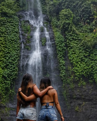 Beautiful young woman with waterfall in forest