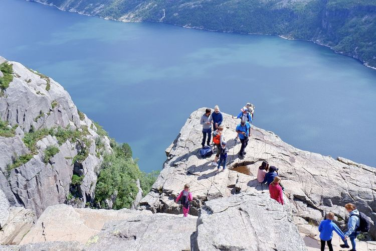 People on rock by mountain