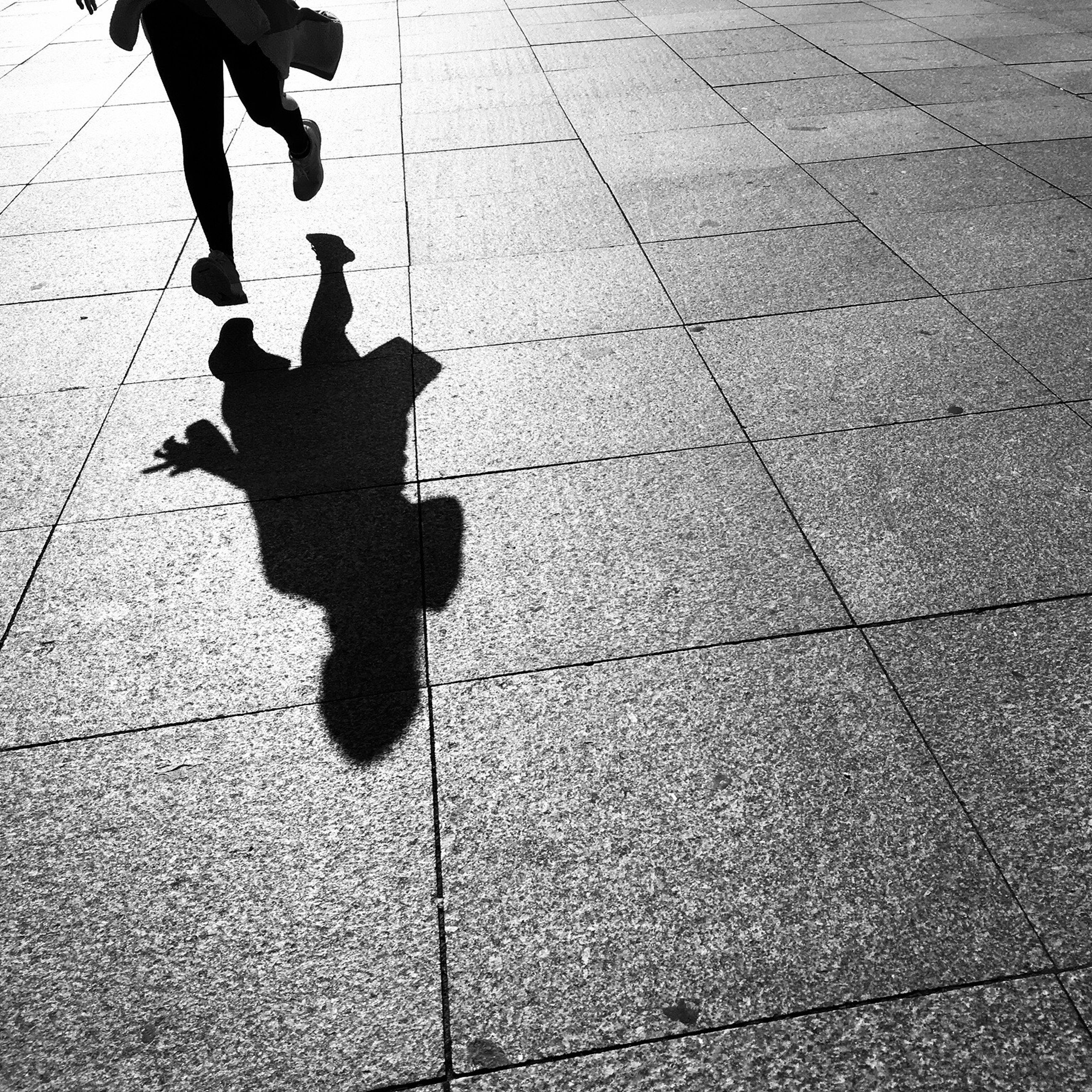 low section, human leg, walking, real people, shadow, men, lifestyles, one person, leisure activity, high angle view, human body part, silhouette, outdoors, only men, day, people, adults only, adult, city
