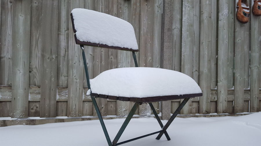 Empty chair on snow covered field during winter