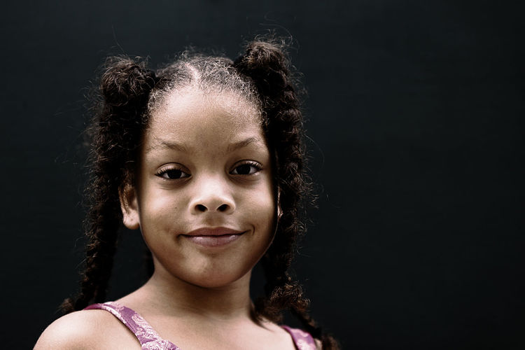 Close-up portrait of smiling girl against black background