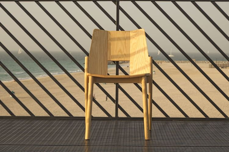Close-up of chair on by fence against sea