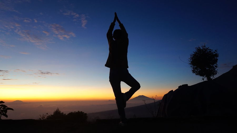 Silhouette man doing yoga against sky during sunset