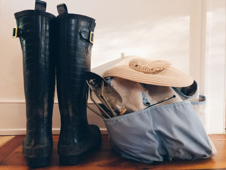 A gardeners bag and straw hat sit next to a pair of rubber gardening boots. Hobbies Wooden Floor Gardening Tools Gardening Gardening Equipment Rain Boots Galoshes EyeEm Selects No People Still Life Indoors  Close-up Clothing Hat Home Interior Wall - Building Feature Personal Accessory Boot Old Day Nature