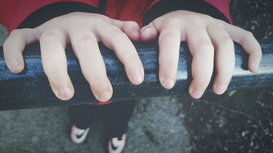 Close-up of boy hands on railing