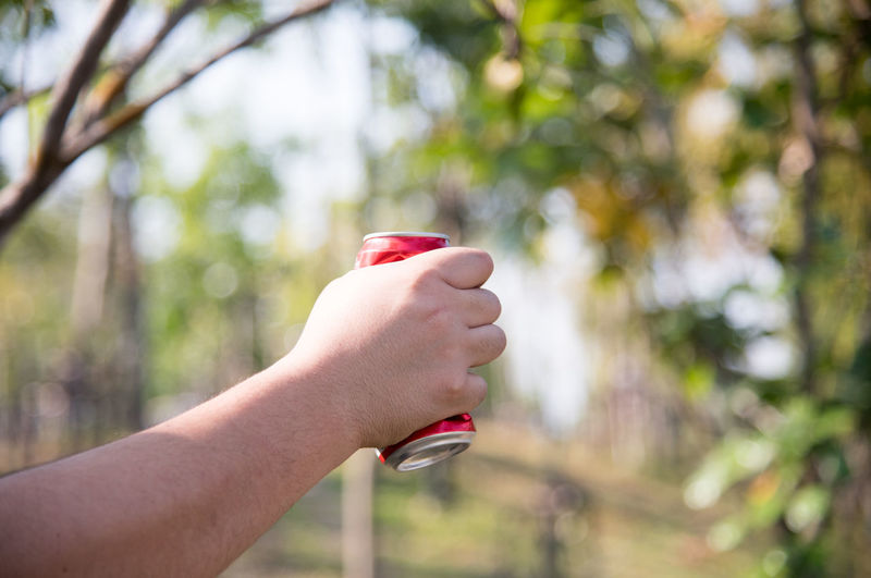 Cropped hand of man crushing drink can outdoors