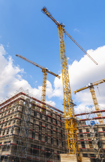 Low angle view of crane by building against sky
