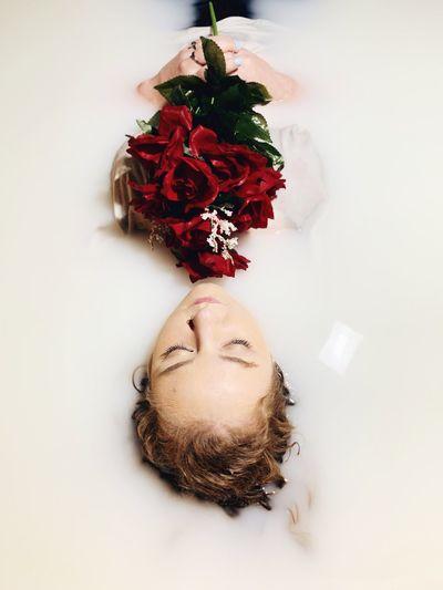 Beautiful woman holding bouquet in bathtub