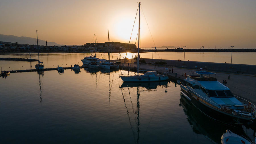 Boats moored in harbor at sunset