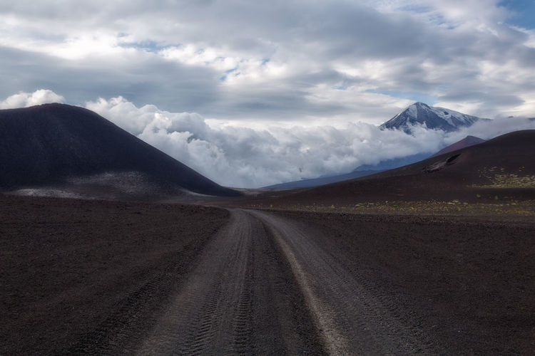 Dirt road amidst landscape and mountains against sky