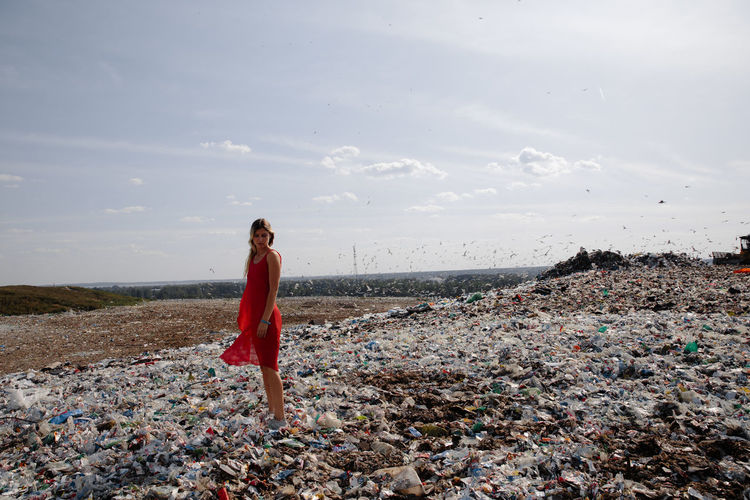 Young woman standing on garbage against sky