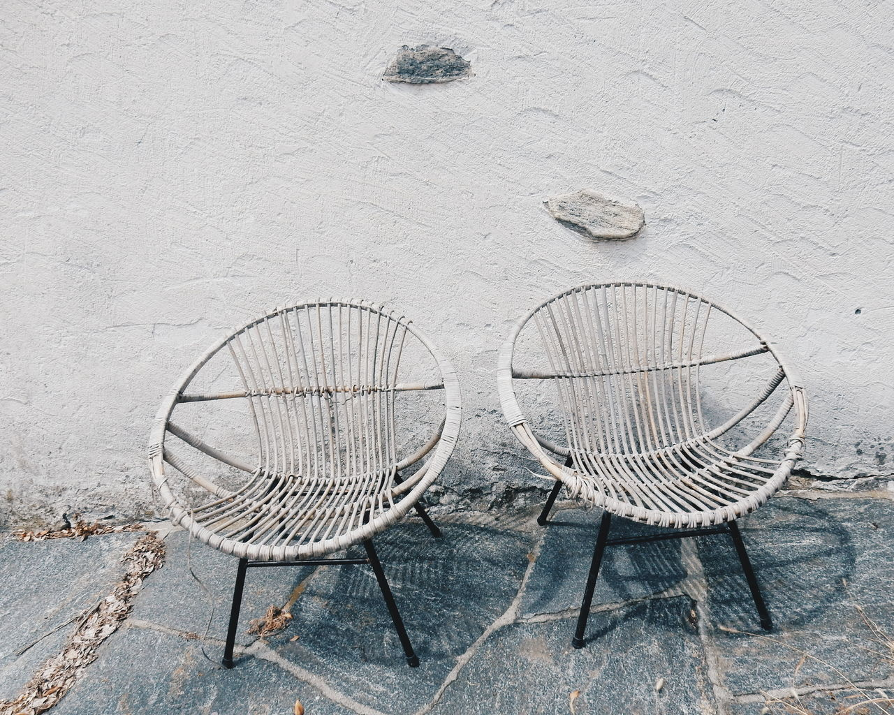 Empty papasan chairs on footpath by white wall