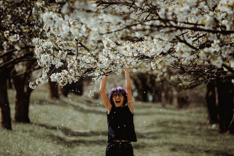 Portrait of smiling young woman standing by cherry blossom tree