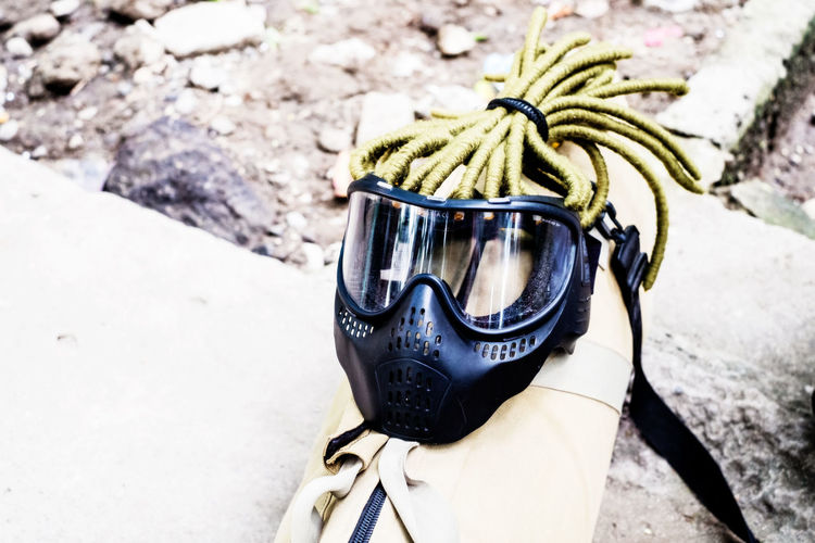 Googles with dreadlocks on creamy rifle case Airsoft Braids Close-up Combat Copy Space Cover Dreadlocks Gear Glasses Google Googles Mask Military No People Outdoors Protection Earth Tone Protective Gear Shooting Sport Sports Tactical Wearables Sports Gear