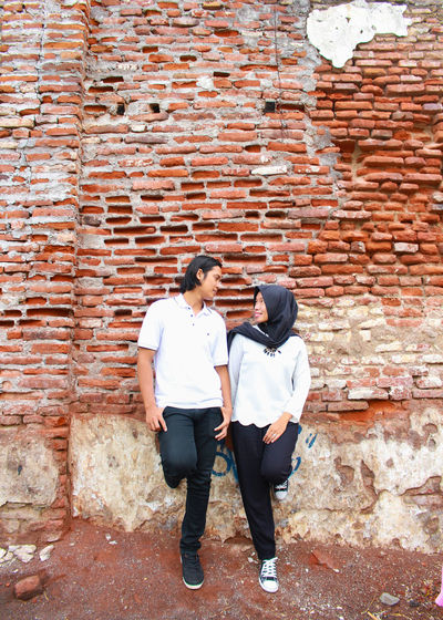 Full length of couple looking each other face to face while standing against brick wall