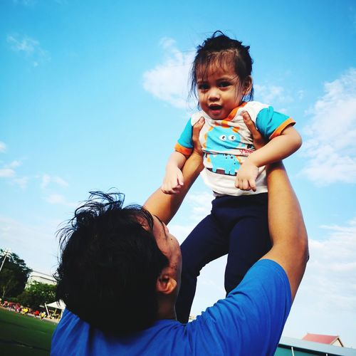 Father Playing With Daughter Against Sky