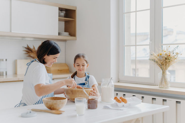 Mother with daughter preparing food in kitchen