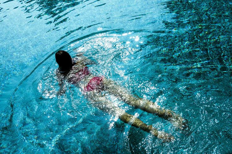 Rear View Full Length Of Woman Wearing Bikini Swimming In Pool