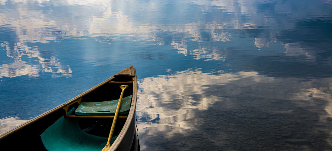 Blue color of the sky and the clouds mirroring on the water around the boat
