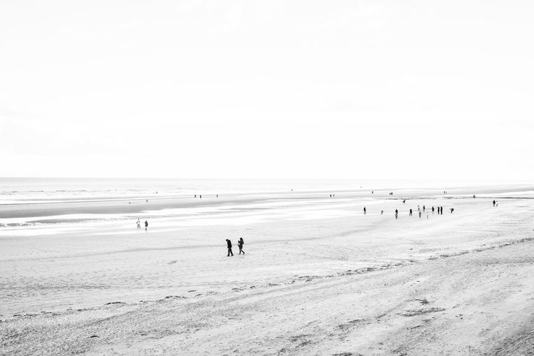 People standing on beach against clear sky
